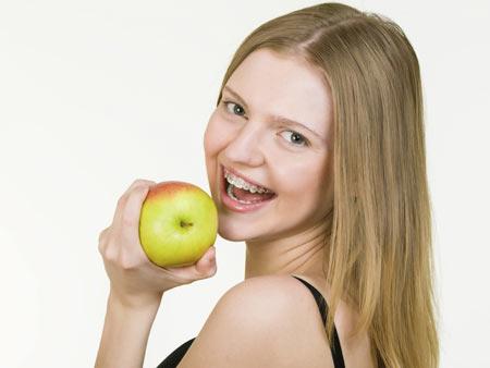 девушка с брекетами кусает яблоко